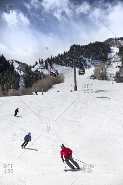 March 17, 2013: USA, Colorado, Aspen, skiers at the base of Aspen Mountain Ski Resort with the gondola in the distance, Ajax