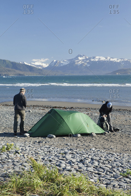 July 11, 2010: USA, Alaska, Homer, travelers set up camp at the end of the Homer Spit, Land's End, with the Kenai Mountains in the background, Kachemak Bay