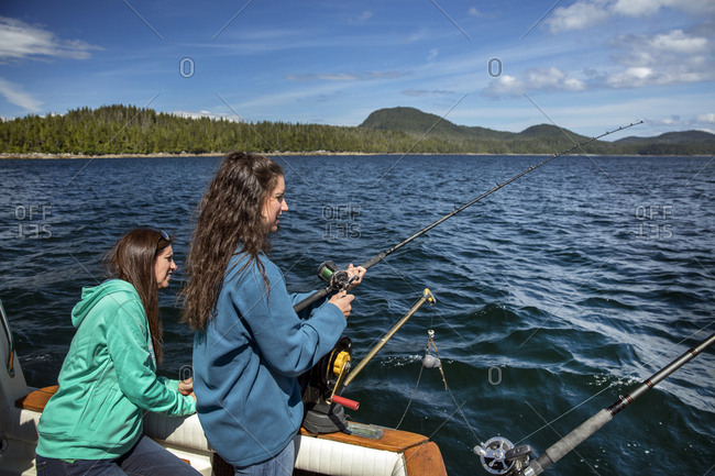 January 1, 2000: USA, Alaska, Ketchikan, two women reel in a fish while fishing the Behm Canal near Clarence Straight, Knudsen Cove along the Tongass Narrows
