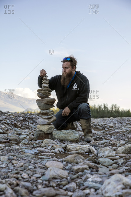 June 29, 2015: USA, Alaska, Denali National Park, a guide builds cairns during a break from the ATV tour to Stampede Ridge