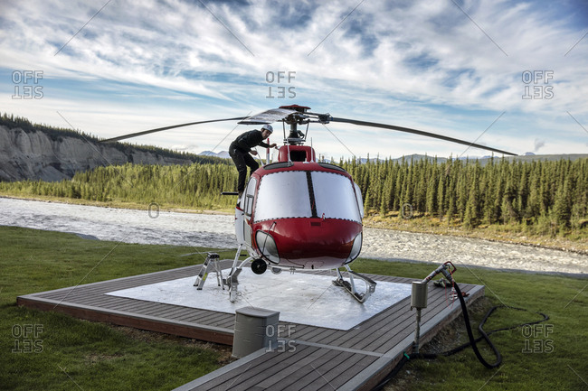 June 29, 2015: USA, Alaska, Denali, Denali National Park, hiking guide and local naturalist Jeffery Ottmers, prepares the helicopter for the helihiking tour