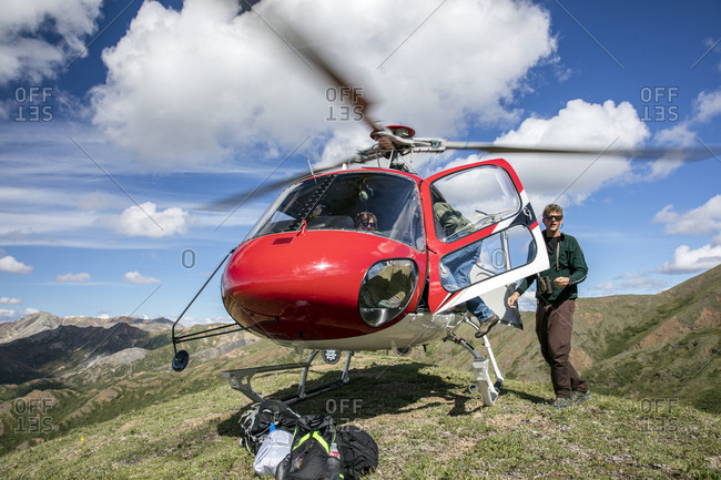 June 29, 2015: USA, Alaska, Denali, Denali National Park, hiking guide and local naturalist Jeffery Ottmers, helps hikers back into the helicopter prior to departure