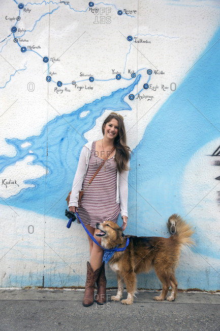 July 1, 2015: USA, Alaska, Anchorage, Local Lauren poses with her dog in front of the Iditarod Mural in downtown Anchorage