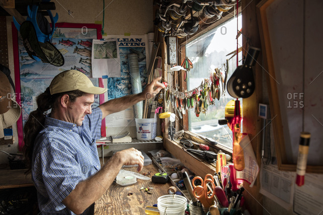 July 29, 2016: USA, Alaska, Homer, China Poot Bay, Kachemak Bay, owners son fixing the collection of fishing lures at the Kachemak Bay Wilderness Lodge
