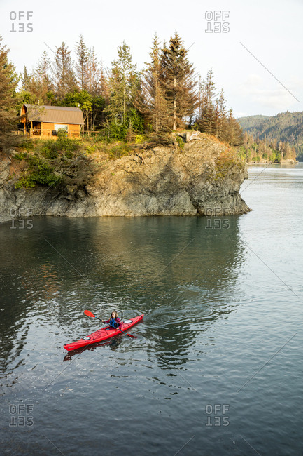 July 30, 2016: USA, Alaska, Homer, China Poot Bay, Kachemak Bay, a kayaker out in the water off of Kachemak Bay Wilderness Lodge