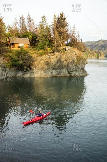 July 30, 2016: USA, Alaska, Homer, China Poot Bay, Kachemak Bay, a kayaker out in the water off of Kachemak Bay Wilderness Lodge