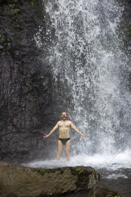 July 15, 2013: INDONESIA, Flores, writer Bernd Schwer takes a dip an cools off, Murukeba Waterfall in Waturaka Village