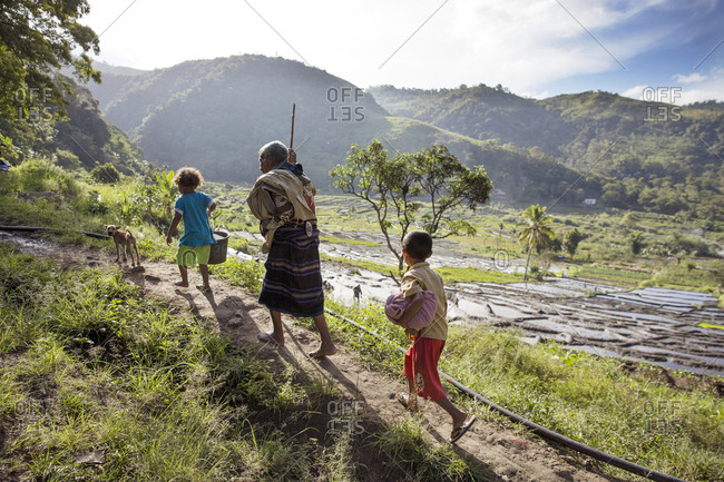 July 15, 2013: INDONESIA, Flores, a grandfather walks with his grandkids and dog in Waturaka Village