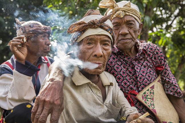 July 16, 2013: INDONESIA, Flores, 100 year old elder Wilhelmus Etu has a smoke with his friends, in Kampung Tutubhada village in Rendu