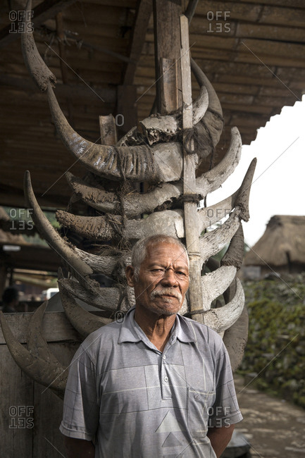 July 17, 2013: INDONESIA, Flores, Bena village, a man stands in front of his home that is adorned in cow horns that were offered to him when he built his home