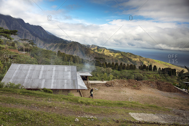 July 18, 2013: INDONESIA, Flores, a man walks in front of his home in the Kajuwala area with views of the Ngada District