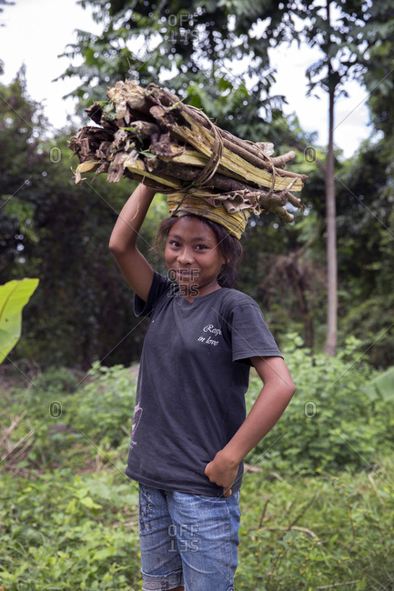 July 19, 2013: INDONESIA, Flores, portrait of a young girl carrying wood on her head in Dintor village