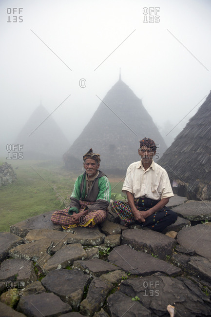 July 20, 2013: INDONESIA, Flores, two leaders of the Wae Rebo Village sit in front of their residences called Mbaru Niang