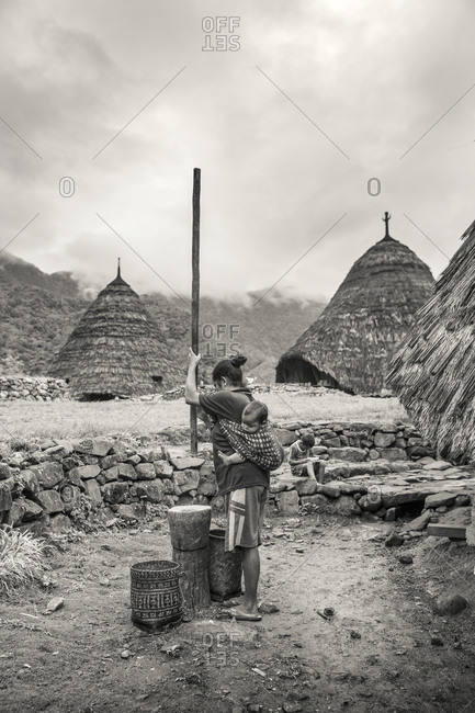 July 20, 2013: INDONESIA, Flores, Rofina Namun and her baby prepare coffee in the mountain village of Wae Rebo