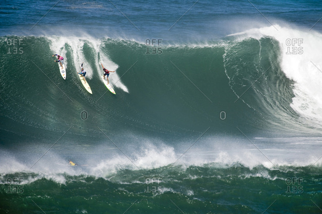 December 8, 2009: USA, Hawaii, the North Shore Oahu, surfers dropping in on a wave at Waimea bay