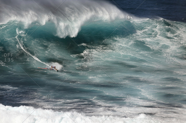 March 15, 2011: USA, Hawaii, Maui, a man windsurfs on huge waves at a break called Jaws or Peahi
