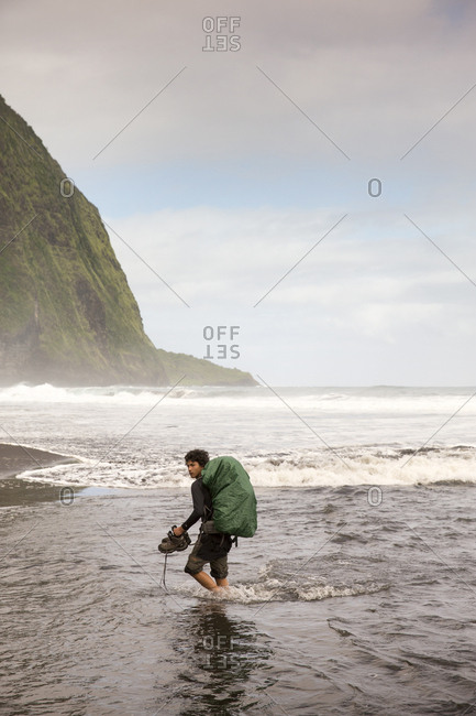 February 27, 2014: USA, Hawaii, The Big Island, backpacker walks on the beach along the surf in the Waipio Valley
