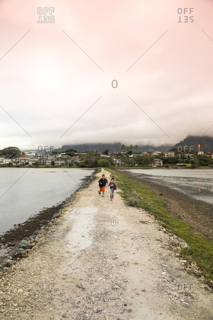 February 7, 2014: USA, Oahu, Hawaii, the son and daughter of Jujitsu martial arts fighter Keith Chang play at the Kaneohe fish pond
