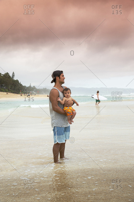 February 9, 2014: USA, Oahu, Hawaii, father and son watch the waves and surfers at Pipeline Beach on the North Shore