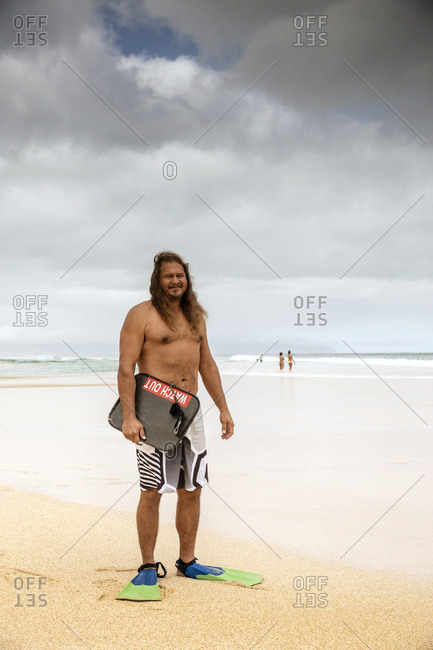 February 9, 2014: USA, Oahu, Hawaii, local North Shore body surfer prepares to get into the water at Pipeline