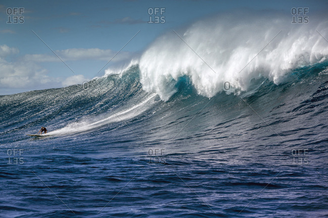 January 17, 2014: USA, HAWAII, Maui, Jaws, big wave surfers taking off on a wave at Peahi on the Northshore