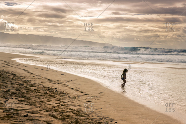 January 16, 2014: USA, HAWAII, Oahu, Northshore, young children play in the water on the beach at Pipeline