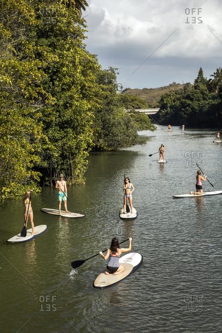 February 28, 2016: HAWAII, Oahu, North Shore, travelers paddleboarding on the Anahulu River below the historic Rainbow Bridge in the town of Haliewa