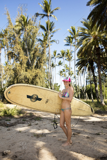 February 29, 2016: HAWAII, Oahu, North Shore, young woman heading out for a surf at Puaena Point Beach Park