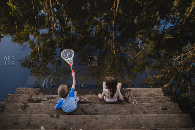 Boy and girl catching fish with net