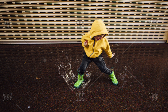 Young boy jumping in puddle