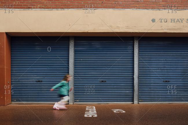 Girl running on asphalt by storage lockers