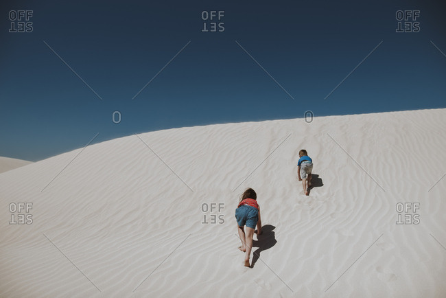 Children climbing up sand dunes