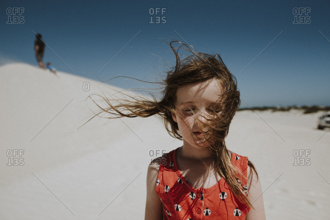 Girl at sand dunes with her hair blowing