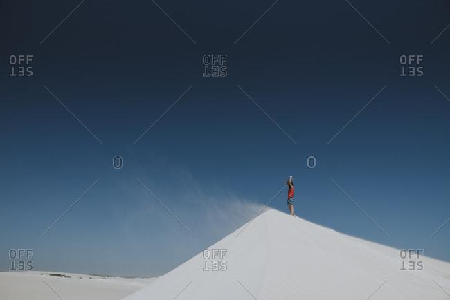 Girl standing on top of sand dune