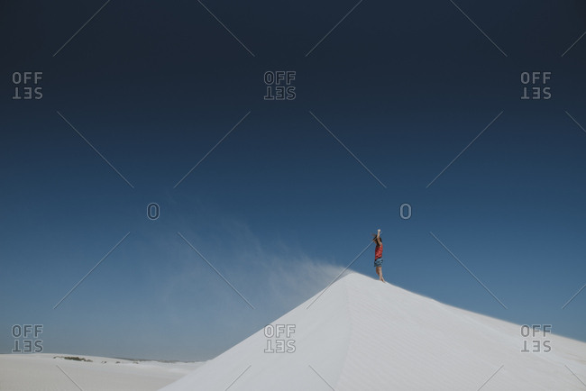 Girl standing on top of sand dune
