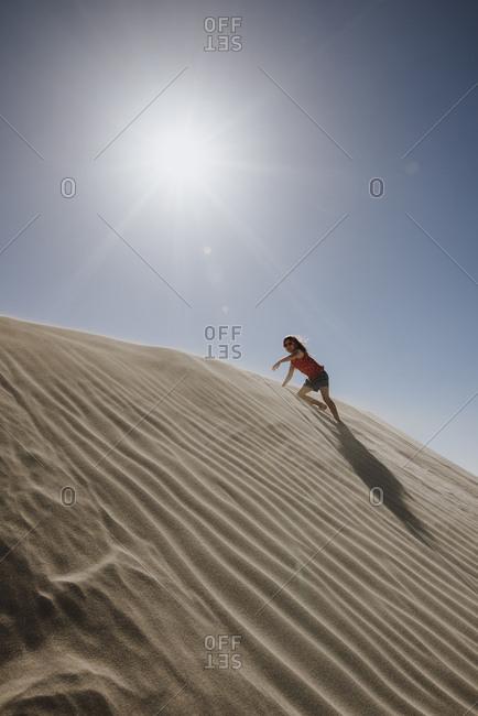 Girl climbing up sand dune