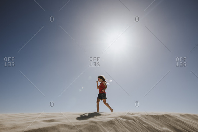 Girl walking on sand dunes