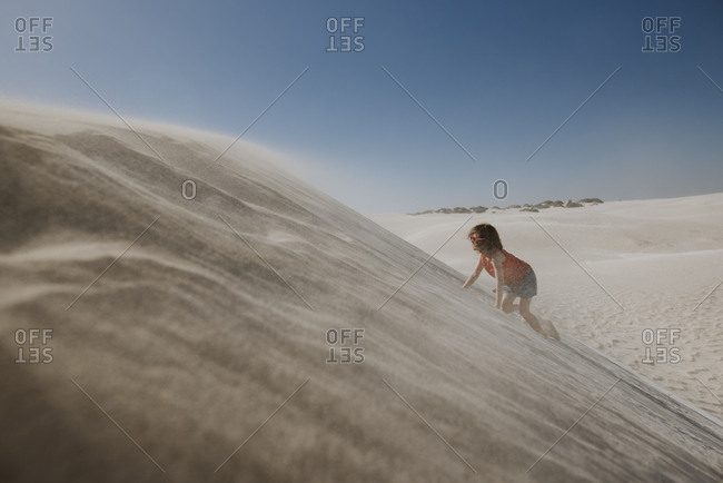 Girl climbing up sand dune with wind blowing