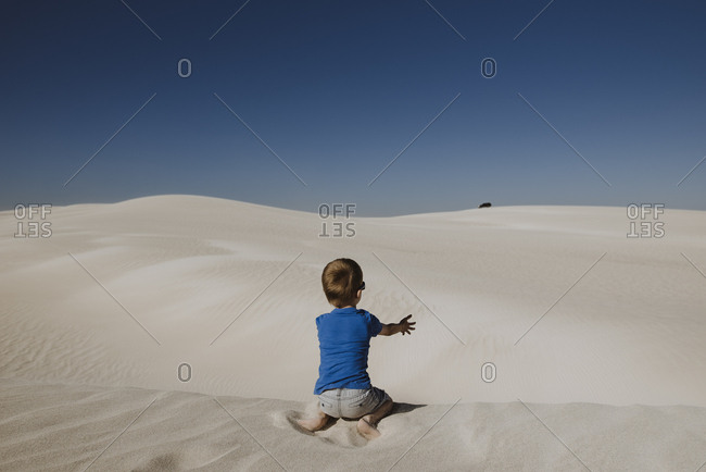 Boy sitting on sand dune