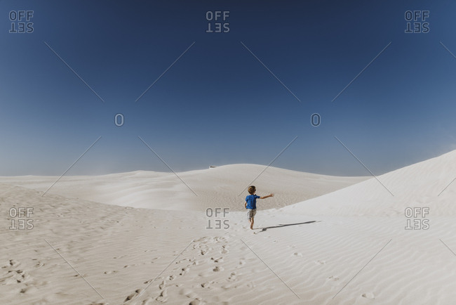 Boy running on sand dunes