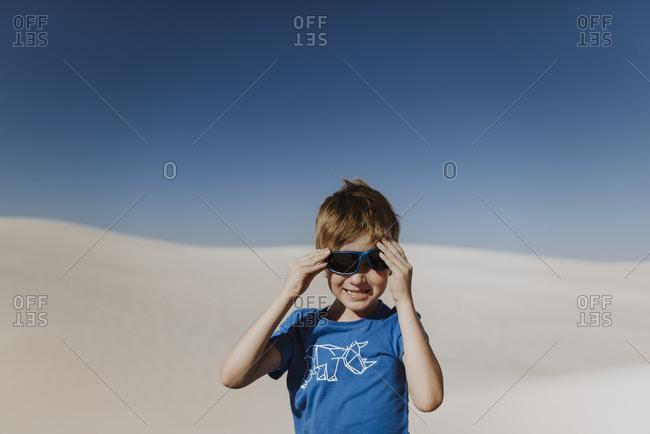 Boy adjusting his sunglasses