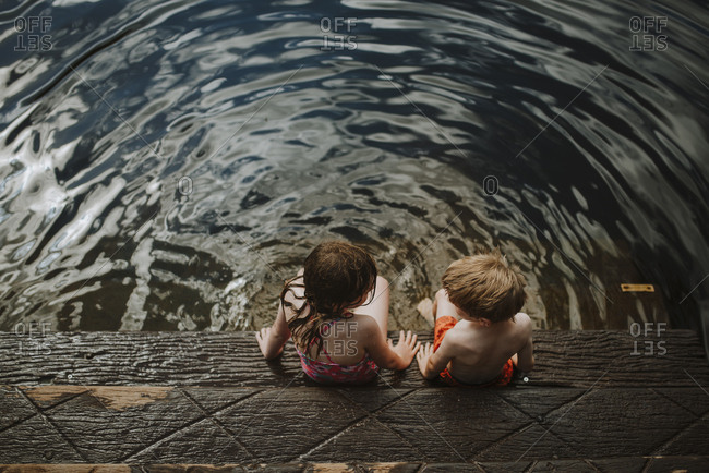 Siblings sitting on wooden steps near river