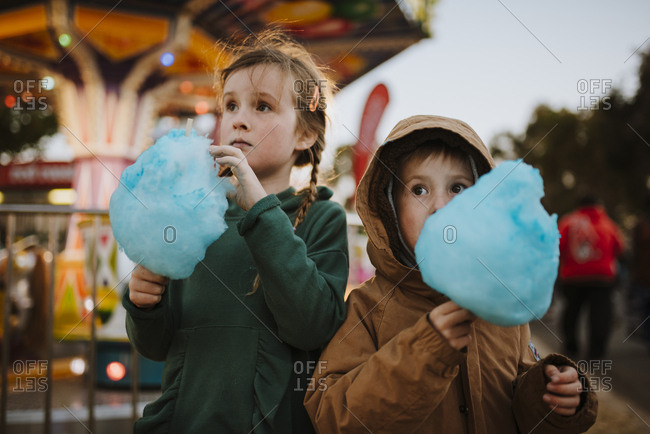 Children eating blue cotton candy at a fair