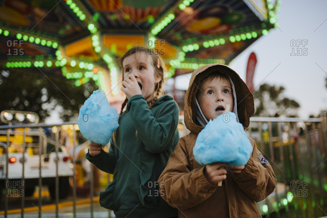 Children eating blue cotton candy at a festival