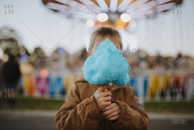 Boy with blue cotton candy at a fair