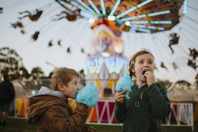 Children eating cotton candy at a fair