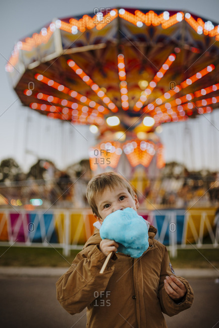Boy eating blue cotton candy at a fair