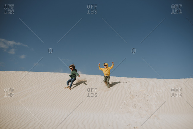 Two children running down a sand dune