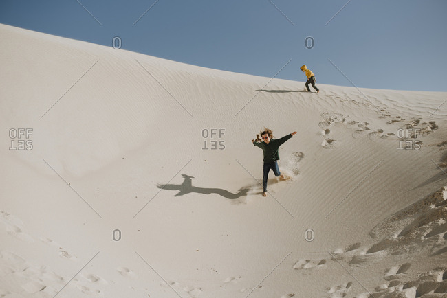 Children running down a sand dune