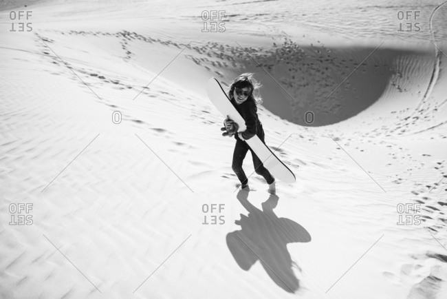 Girl carrying a sand board up a sand dune